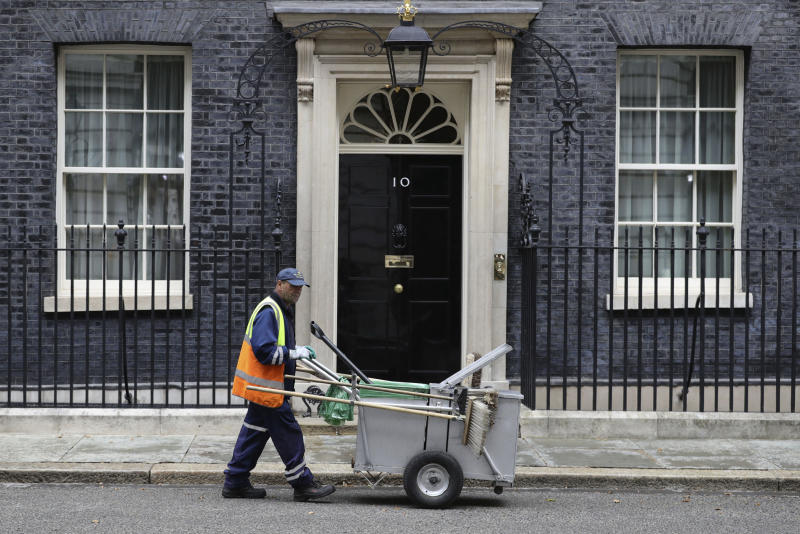 A street cleaner outside 10 Downing Street in London, Wednesday July 31, 2019.  British Prime Minister Boris Johnson is away from Downing street on a national tour to visit Scotland, Wales and Northern Ireland, seeking to reassure voters and regional politicians that Britain's Brexit split from Europe won't hurt the economy in the longterm or rip the U.K. apart. (Aaron Chown/PA via AP)