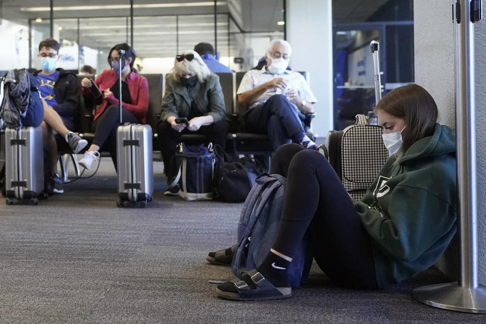 Passenger Cari Driggs, right, from Provo, Utah, waits to board a United Airlines flight to Hawaii for vacation at San Francisco International Airport in San Francisco, Thursday, Oct. 15, 2020. Coronavirus weary residents and struggling business owners in Hawaii will be watching closely as tourists begin to return to the islands on Thursday without having to self-quarantine upon arrival. (AP Photo/Jeff Chiu)