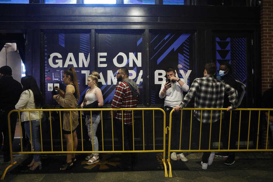 People stand close to one another in line along yellow fencing outside a venue, most without face masks