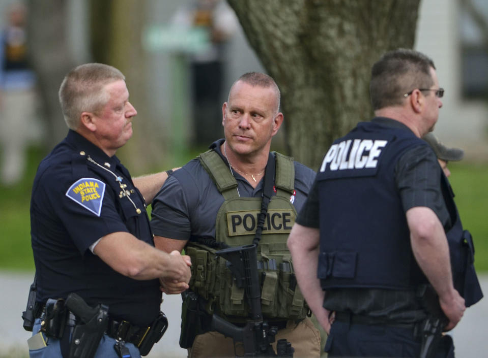Indiana State Police Sgt. Joe Watts, left, consoles Terre Haute Chief of Police John Plasse, centre, at the scene of the fatal shooting. Source: AP
