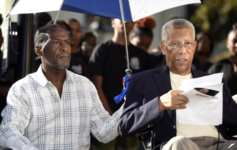 In this Friday, Oct. 11, 2019 photo, actor Russell Joel Brown, left, holds an umbrella to shade Ellis Johnson as he talks about the life of Jessye Norman during the Jessye Norman Boulevard honorary street naming ceremony in Augusta, Ga. The city renamed a street for Norman outside the Jessye Norman School of the Arts, which she opened in 2003 to provide free fine arts education to disadvantaged children. (Michael Holahan/The Augusta Chronicle via AP)