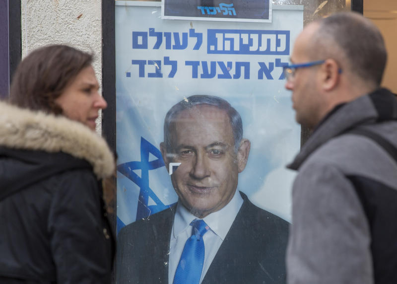 People look at a poster of Israel Prime Minister and governing Likud party leader Benjamin Netanyahu at a voting center in the northern Israeli city of Hadera, Thursday, Dec. 26, 2019. Israel's governing Likud party was holding primaries on Thursday, in the first serious internal challenge to Israeli Prime Minister Benjamin Netanyahu in his more than a decade in power.  (AP Photo/Ariel Schalit)