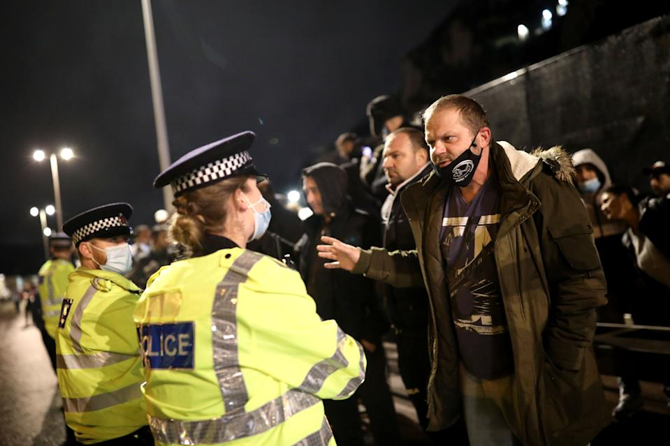 DOVER, ENGLAND - DECEMBER 22: Police officers speak to a group of lorry drivers as the Port of Dover remains closed on December 22, 2020 in Dover, United Kingdom. Over 1500 lorries remained stacked up around Kent as drivers waited for a resumption of travel from the port of Dover to France. On Sunday, France abruptly halted freight and passenger travel from the UK over concerns about the UK's surging covid-19 cases and a new variant of the virus. (Photo by Dan Kitwood/Getty Images)