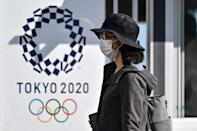 A woman walks past a Tokyo 2020 poster wearing a mask to prevent coronavirus transmission