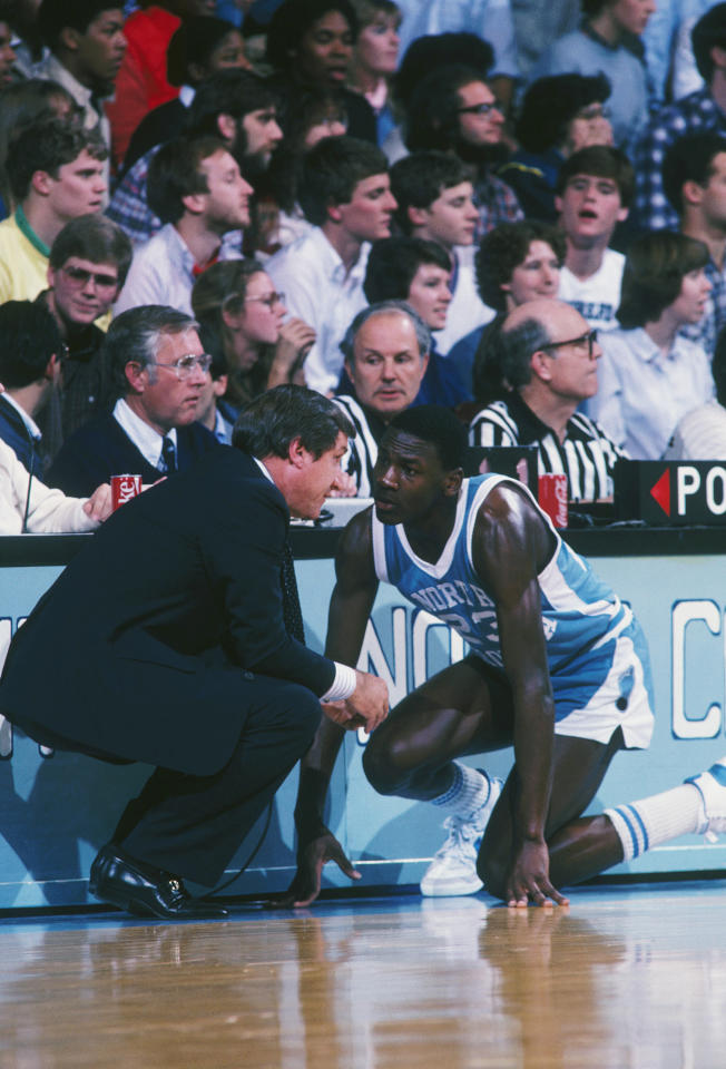 Michael Jordan receives some instructions from his college coach Dean Smith before checking into a game. (Getty Images)