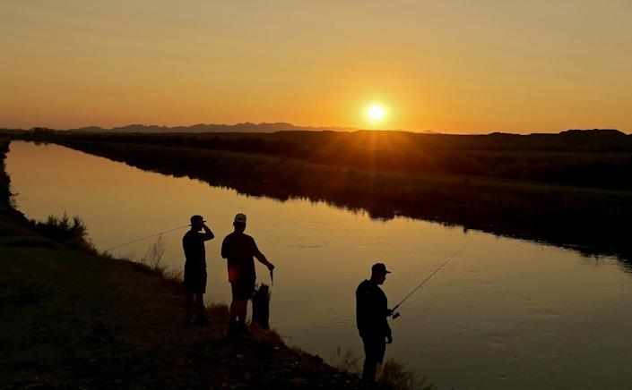 Anglers set their lines at an irrigation canal in Blythe.