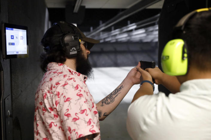 Firearms trainer Kevin Burke, left, instructs new gun owner Troy Deguzman during a shooting session at Maxon Shooter's Supplies and Indoor Range, Friday, April 30, 2021, in Des Plaines, Ill. After a year of pandemic lockdowns, mass shootings are back, but the guns never went away. As the U.S. inches toward a post-pandemic future, guns are arguably more present in the American psyche and more deeply embedded in American discourse than ever before. The past year's anxiety and loss fueled a rise in gun ownership across political and socio-economic lines. (AP Photo/Shafkat Anowar)