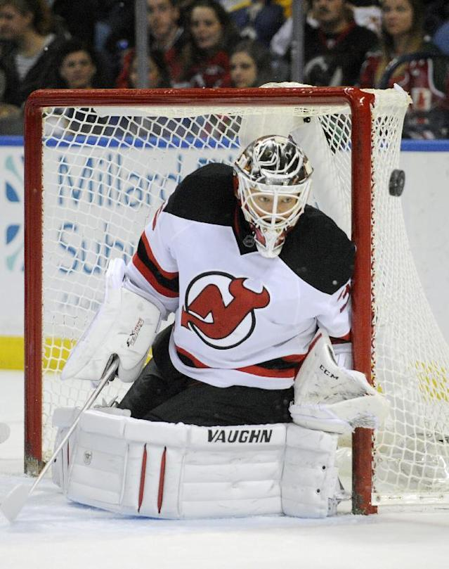 New Jersey Devils goaltender Cory Schneider eyes an incoming puck during the first period of an NHL hockey game against the Buffalo Sabres in Buffalo, N.Y., Tuesday, April 1 2014. (AP Photo/Gary Wiepert)