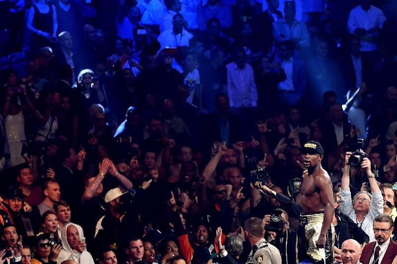 The crowd take smartphone photos of Floyd Mayweather as he celebrates his unanimous decision victory against Manny Pacquiao on May 2, 2015 at the MGM Grand Garden Arena (AFP Photo/Jason Merritt)