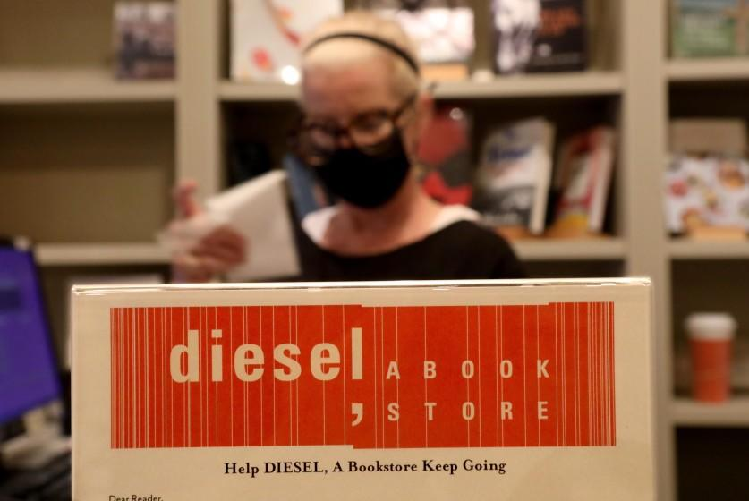 """Diesel bookseller Lynn Aime makes a sale next to a sign asking customers to contribute to the shop's GoFundMe. <span class=""""copyright"""">(Genaro Molina / Los Angeles Times)</span>"""