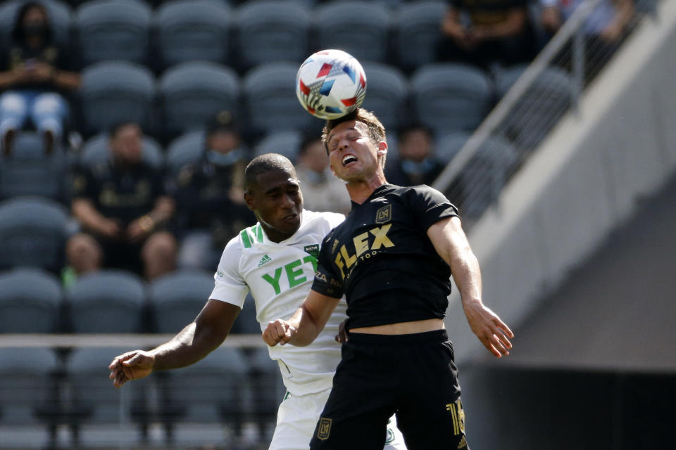 Los Angeles FC forward Danny Musovski, right, heads the ball next to Austin FC defender Jhohan Romana during the first half of an MLS soccer match Saturday, April 17, 2021, in Los Angeles. (AP Photo/Ringo H.W. Chiu)