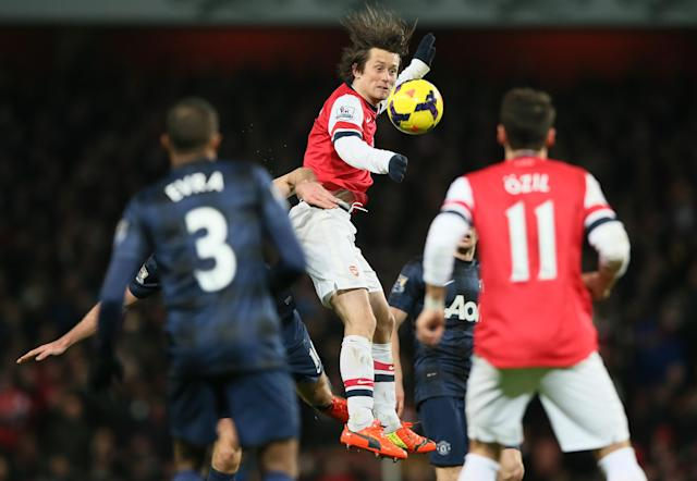 Arsenal Tomas Rosicky, centre, heads the ball forward during the English Premier League soccer match between Arsenal and Manchester United at the Emirates stadium in London, Wednesday, Feb. 12, 2014. (AP Photo/Alastair Grant)