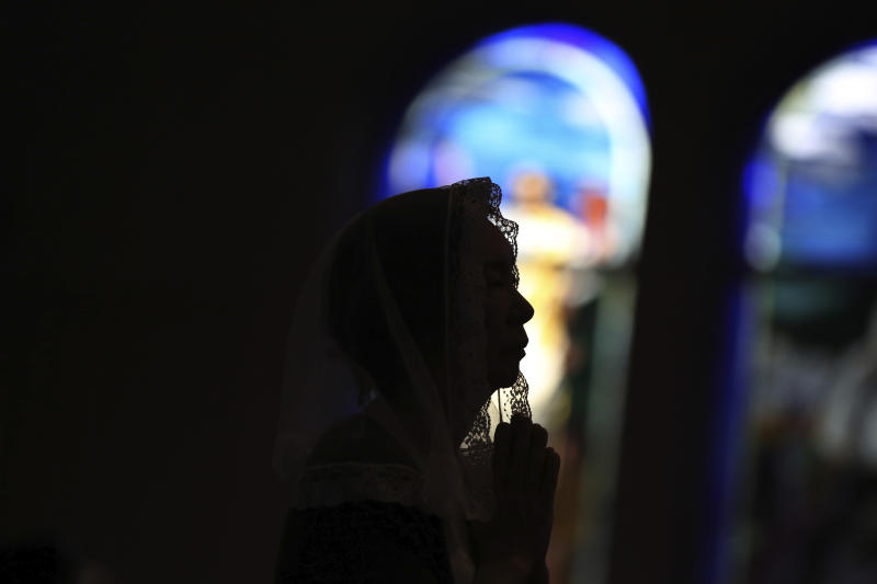 FILE - In this Aug. 9, 2015, file photo, a Catholic offers prayers at an early morning Mass to pay respect to the victims of the atomic bombing at the Urakami Cathedral in Nagasaki, southern Japan. The Vatican said Friday, Sept. 13, 2019, Pope Francis will visit Thailand and Japan on Nov. 19-26. (AP Photo/Eugene Hoshiko, File)
