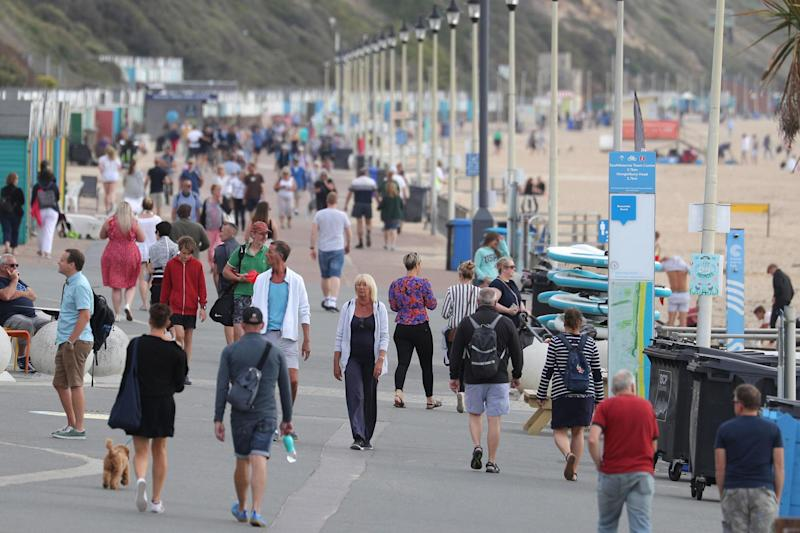 People walk along the beach front at Boscombe beach in Dorset on Saturday (PA)