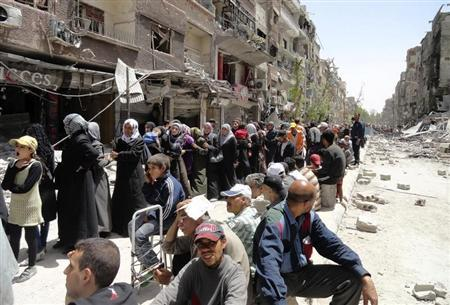 Residents queue as they wait to receive food aid distributed by the UNRWA at the Palestinian refugee camp of Yarmouk