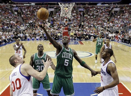 Boston Celtics' Kevin Garnett (5) reaches for a rebound as Philadelphia 76ers' Spencer Hawes (00) and Thaddeus Young (21) look on in the first half of an NBA basketball game on Friday, March 23, 2012, in Philadelphia. (AP Photo/Matt Slocum)
