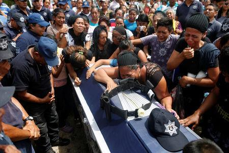 Relatives mourn on top of the coffin of police officer Juan Jimenez, who was a victim of the earthquake that struck the southern coast of Mexico late on Thursday, during his burial in Juchitan, Mexico, September 10, 2017. REUTERS/Carlos Jasso