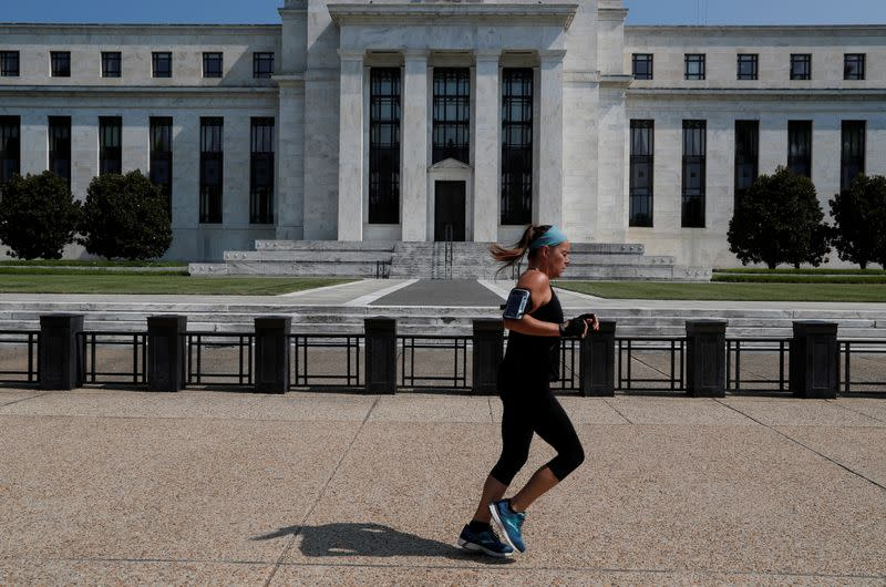 FILE PHOTO: Woman jogs past the Federal Reserve building in Washington