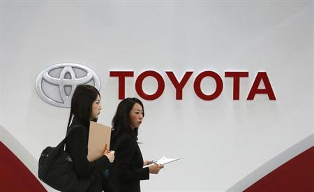 Women walk in front of Toyota Motor's logo at the company's showroom in Tokyo