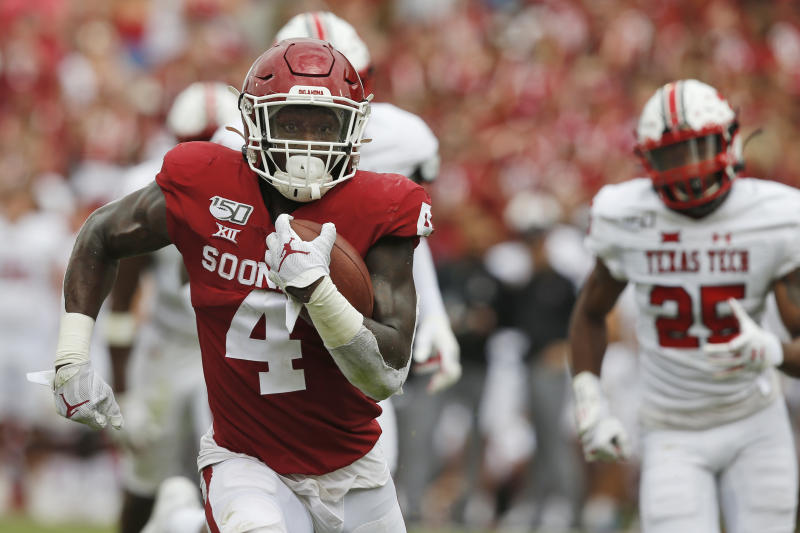 Oklahoma running back Trey Sermon (4) carries for a touchdown in front of Texas Tech defensive back Dadrion Taylor (25) in the third quarter of an NCAA college football game in Norman, Okla., Saturday, Sept. 28, 2019. (AP Photo/Sue Ogrocki)