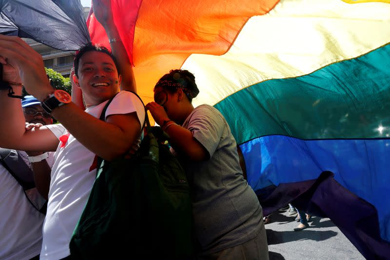 FILE PHOTO: Revellers smile as they hold a giant rainbow during the gay pride parade in Caracas, Venezuela