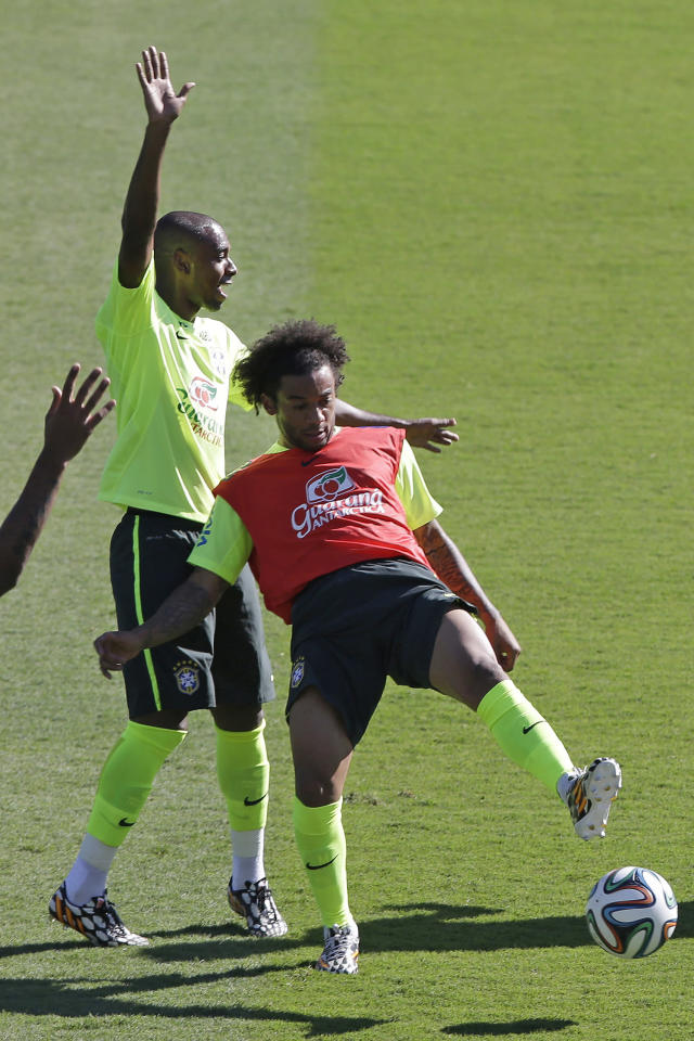 Brazil's Marcelo, right, and Fernandinho train one day before his team's round of 16 World Cup soccer match with Chile at Mineirao Stadium in Belo Horizonte, Brazil, Friday, June 27, 2014. (AP Photo/Andre Penner)