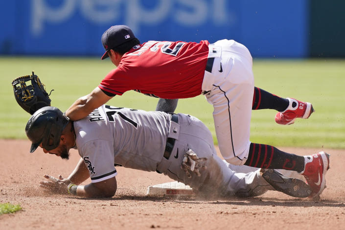 Chicago White Sox's Jose Abreu, bottom, is safe at second base as Cleveland Indians' Yu Chang lets the ball get by in the sixth inning of the first baseball game of a doubleheader, Monday, May 31, 2021, in Cleveland. Indians' Cesar Hernandez was charged with a throwing error. (AP Photo/Tony Dejak)