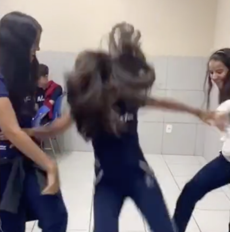 Two girls shown teaming up to kick the legs of another girl so she falls back onto the tiles. Source: TikTok via Facebook