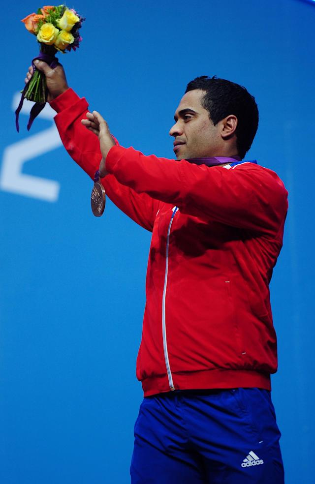 LONDON, ENGLAND - AUGUST 01: Bronze medalist Ivan Cambar Rodriguez of Cuba celebrates on the podium during the medal ceremony after the Men's 77kg Weightlifting on Day 5 of the London 2012 Olympic Games at ExCeL on August 1, 2012 in London, England. (Photo by Laurence Griffiths/Getty Images)