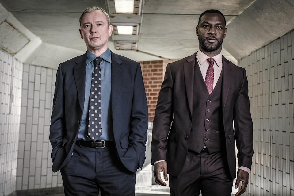 ITV STUDIOS FOR ITV GRACE SERIES 1 DEAD SIMPLE  Pictured:JOHN SIMM as DS Roy Grace and RICHIE CAMPBELL as DS Branson.  This image is the copyright of ITV and may only be used in direct relation to Grace series 1,2021.