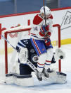 Winnipeg Jets goaltender Connor Hellebuyck (37) makes a save as Montreal Canadiens' Corey Perry (94) screens him during the second period of an NHL hockey game Saturday, Feb. 27, 2021, in Winnipeg, Manitoba. (John Woods/The Canadian Press via AP)