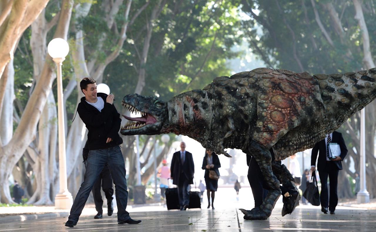 """SYDNEY, AUSTRALIA - AUGUST 28: In this handout provided by Destination New South Wales, a Tyrannosaurus rex takes a morning stroll with commuters in Hyde Park on August 28, 2013 in Sydney, Australia. In a world first, the Australian Museum presents """"Tyrannosaurs: Meet the Family"""", an innovative, multimedia experience showcasing the newly-revised tyrannosaur family tree. With over 10 life-sized dinosaur specimens on display, including one of the oldest tyrannosaurs, Guanlong wucaii, the exhibition runs from 23 November 2013 to 27 July 2014. Showcasing a dramatic array of fossils and casts of tyrannosaur specimens, including neverbefore-seen specimens from China, """"Tyrannosaurs: Meet the Family"""" is designed to provide a snapshot of dinosaur life and show how this group became the world's top predators with their massive skulls, powerful jaws and bone-crunching teeth. (Photo by James Morgan/Destination New South Wales via Getty Images)"""
