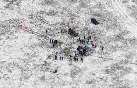 A search and rescue team approaches the Soyuz TMA-13M capsule with the International Space Station (ISS) crew of Alexander Gerst of Germany, Maxim Surayev of Russia and Reid Wiseman of the U.S. after its landing near the town of Arkalyk in northern Kazakhstan, November 10, 2014. REUTERS/Shamil Zhumatov