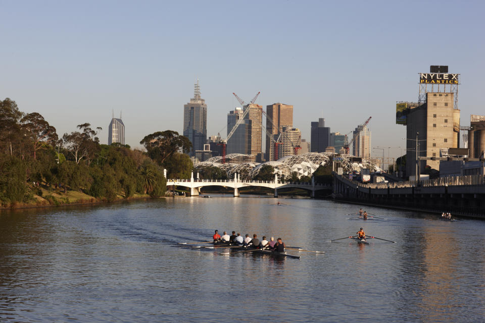 Rowers on Yarra River at Richmond with Hoddle Bridge, Nylex sign, AAMI Park and CBD in background. - stock photo Melbourne, Victoria, Australia, Australasia