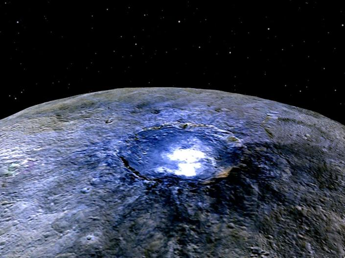 This representation of Ceres' Occator Crater in false colours shows differences in the surface composition. Scientists use the false colour as a way of examining the way that the surface is composed: NASA/JPL-Caltech/UCLA/MPS/DLR/IDA