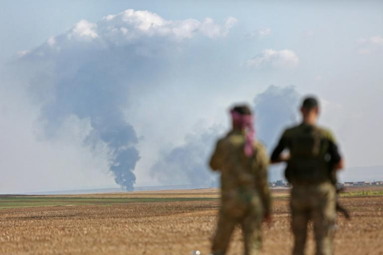 Turkey-backed Syrian fighters watch as smoke billows in the distance during clashes between Syrian regime forces, and Turkish forces, 15kms east of the northeastern town of Ras al-Ein, on October 30, 2019