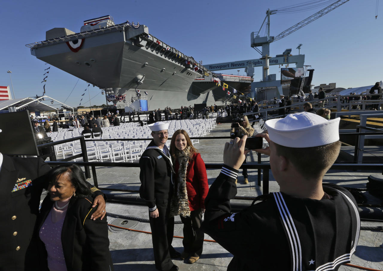 U.S. Navy Bosons mate, Ben Hansen and his wife Jessica, of Edmore Mich., are photographed in front of the Navy's newest nuclear powered aircraft carrier USS Gerald R. Ford for the christening of the ship at the Newport News Shipbuilding in Newport News, Va., Saturday, Nov. 9, 2013. Former President Ford's daughter Susan Ford Bales will christen the ship. (AP Photo/Steve Helber)