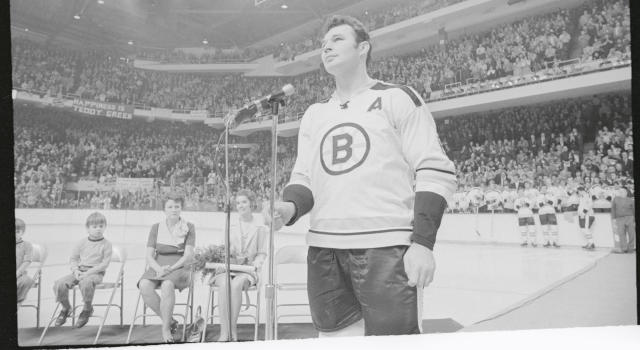 Ted Green, Boston Bruins' defenseman (right) looks up at Boston Garden 14,000 fans who applaude him during ceremonies honoring him. Looking on are Ted's wife Pat (2nd right), his mother Mrs. John Green, and one of Ted's children, Chris. The Bruins defenseman was honored for his amazing comeback from a head injury which kept him from playing a year. (Getty Images)
