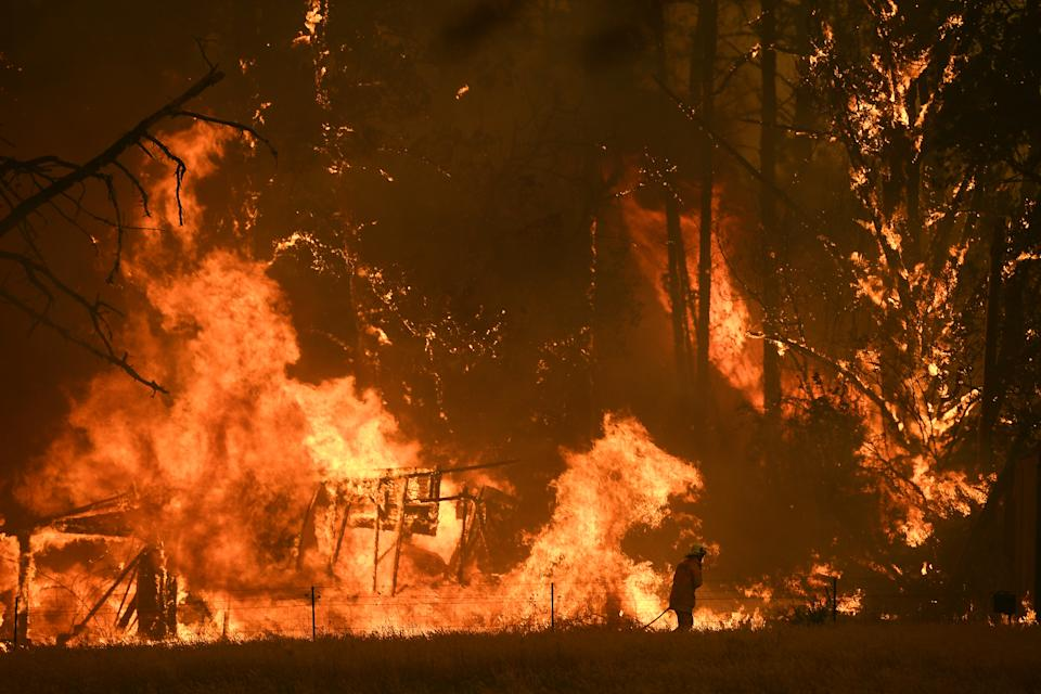 Fire crews fight the Gospers Mountain Fire as it impacts a structure at Bilpin.