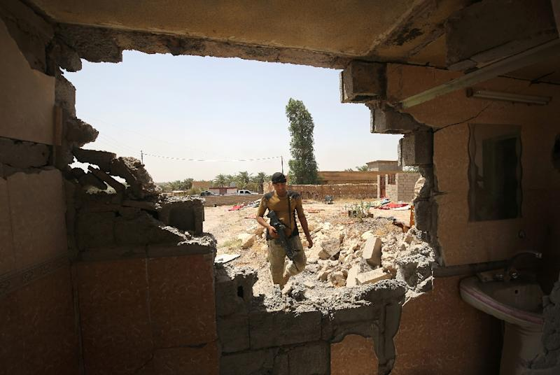 An Iraqi fighter is seen through a damaged wall as he takes part in an operation to retake al-Shahabi village from the Islamic State (IS) group, on May 24, 2016