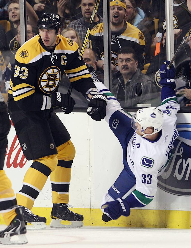 BOSTON, MA - JANUARY 07:  Zdeno Chara #33 of the Boston Bruins checks Henrik Sedin #33 of the Vancouver Canucks on January 7, 2012 at TD Garden in Boston, Massachusetts.  (Photo by Elsa/Getty Images)
