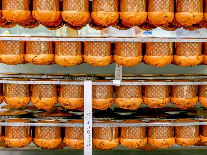 Panettone cakes are seen on a rack at the Pasticceria Giotto in Padua's Due Palazzi prison December 2, 2014. White-coated bakers are chopping nuts, dipping pastry into liquid chocolate and hanging freshly baked panettone Christmas cake upside down to preserve its domed shape. But when one of the all-male team steps outside to smoke, he is in a barred enclosure attached to Padua prison. Sweet smells have wafted through this building since 2005, when the local Giotto cooperative opened the 'Pasticceria Giotto', which they say is Italy's only bakery inside a jail. Picture taken December 2, 2014.