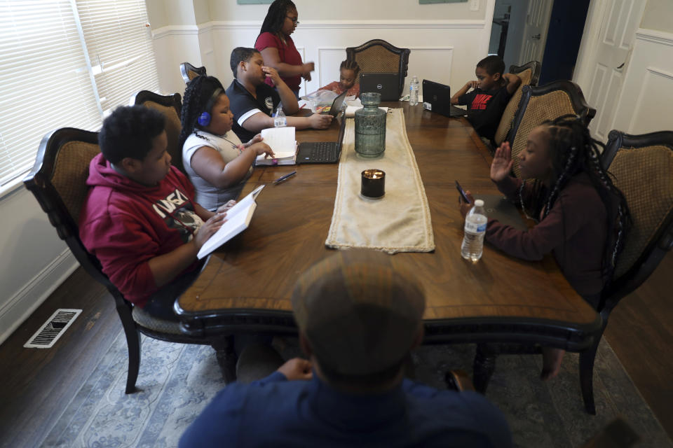 The Preston family children work diligently on their studies around the dining room table at their residence in Chicago's South Side neighborhood, Wednesday, Feb. 10, 2021, in Chicago. (AP Photo/Shafkat Anowar)