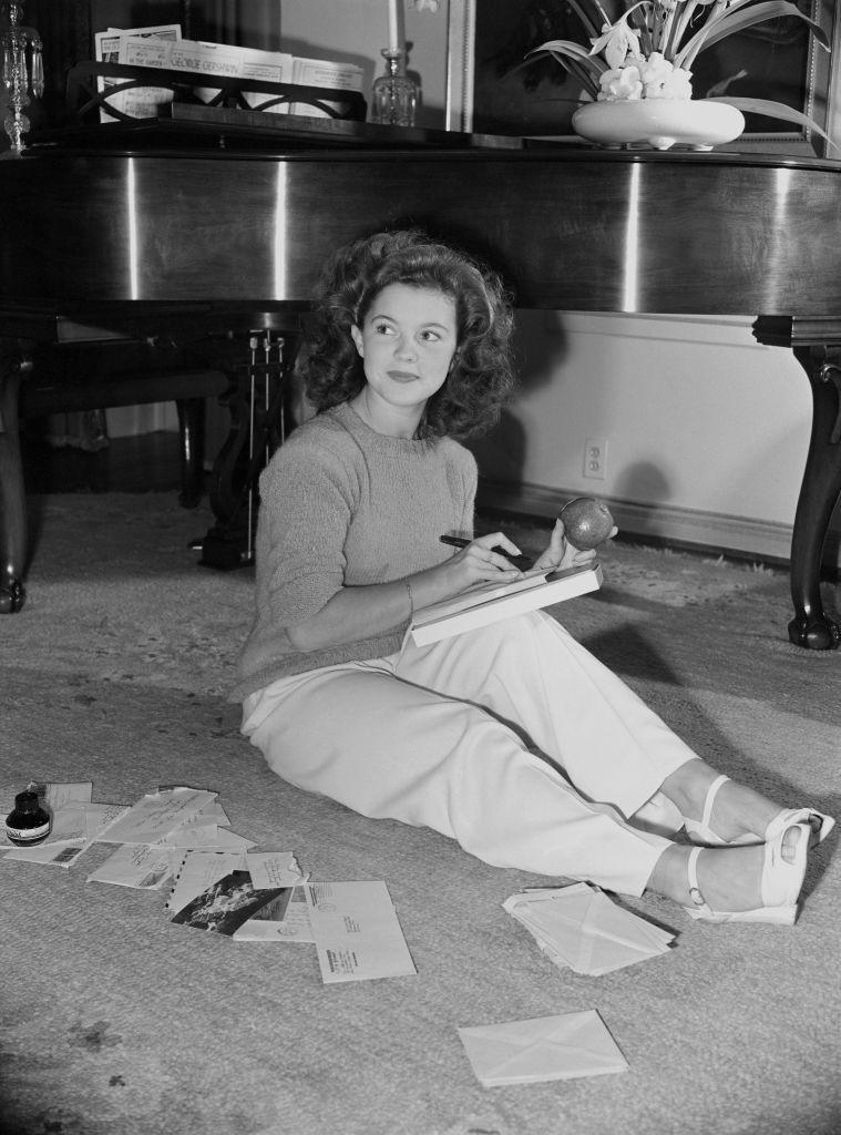 <p>The former child star takes a moment to read some mail and enjoy an apple on the floor of her Los Angeles living room, circa 1944.</p>