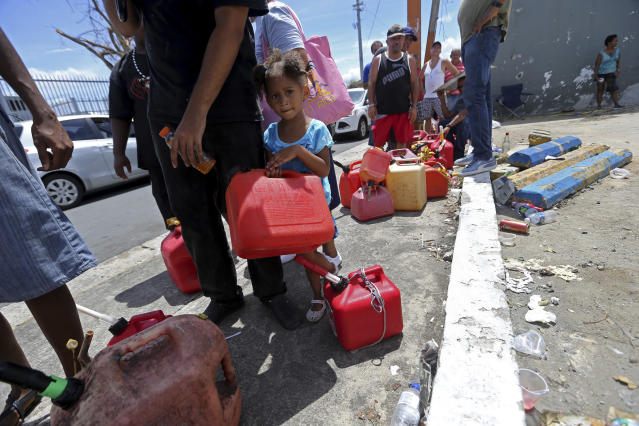 Abi de la Paz de la Cruz, 3, holds a gas can as she waits in line with her family, San Juan, Puerto Rico, Sept. 25, 2017. (Photo: Gerald Herbert/AP)