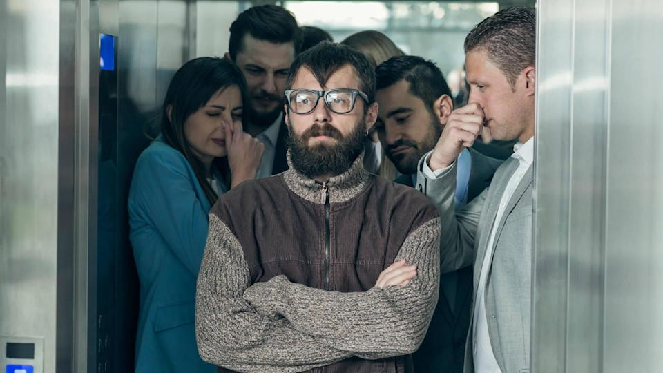A dirty hipster affecting his coworkers in an elevator.