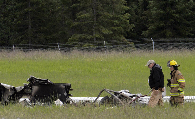 Investigators look at the remains of a fixed-wing aircraft that was engulfed in flames Sunday July 7, 2013 at the Soldotna Airport in Soldotna, Alaska. Authorities say an air taxi has crashed, killing all 10 people on board. (AP Photo/Peninsula Clarion, Rashah McChesney)