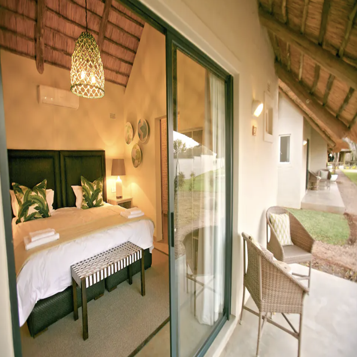 Room at villa with modern jungle design and porch seating for two.