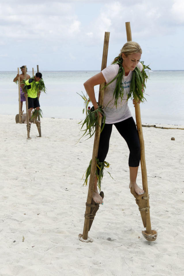 """Loose Lips Sink Ships""-- In this Road Block, Max (left) and Caroline (right) must balance on traditional Polynesian sparring stilts and kick a coconut across a beach in order to receive the next clue on ""The Amazing Race."""