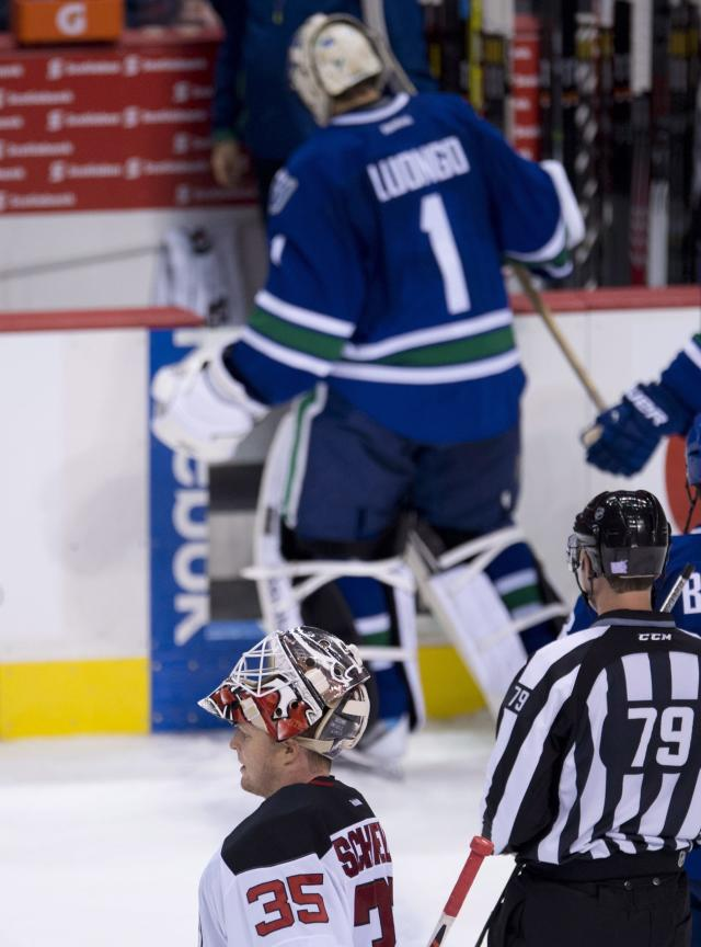 New Jersey Devils goalie Cory Schneider (35) skates past a former teammate, Vancouver Canucks goalie Roberto Luongo (1), following the second period of an NHL hockey game Tuesday, Oct. 8, 2013, in Vancouver, British Columbia. (AP Photo/The Canadian Press, Jonathan Hayward)